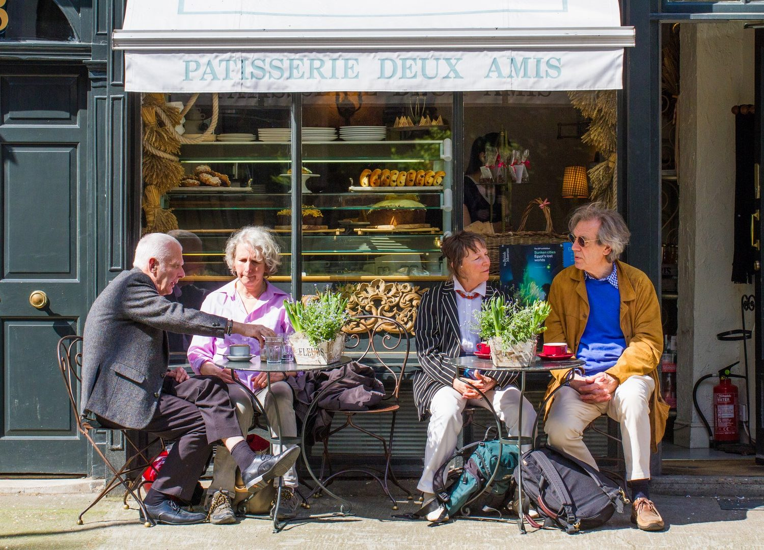 London, UK - May 5, 2016. Elderly tourist couples sitting outside at a French patisseries tables and enjoying a well earned rest after touring the streets of London.